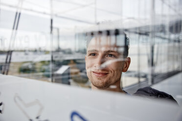 Portrait of smiling young man at the airport looking out of window - RHF02284