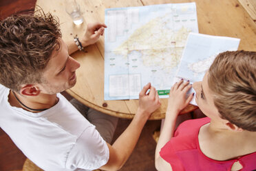 Young couple sitting at table at home with map - RHF02290