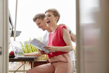 Happy couple on balcony at home with laptop and map - RHF02293