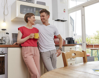 Happy couple at home having a coffee break in kitchen - RHF02299