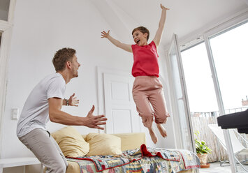 Excited couple in living room at home - RHF02302