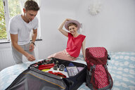 Happy couple packing suitcase for summer vacation on bed - RHF02308