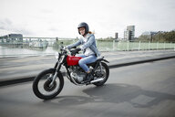 Germany, Cologne, young woman riding motorcycle on bridge - RHF02320