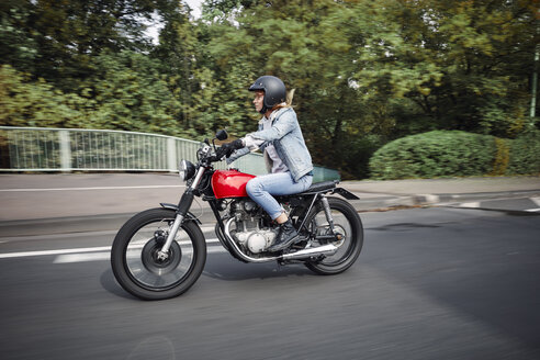 Young woman riding motorcycle on a street - RHF02323