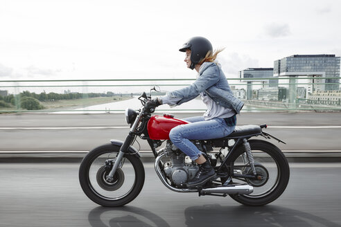 Germany, Cologne, young woman riding motorcycle on bridge - RHF02326