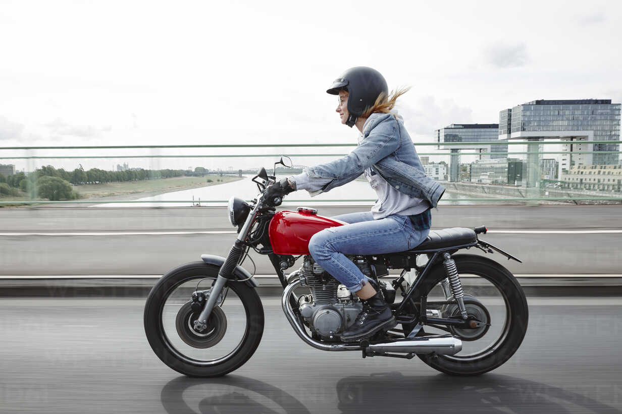 Germany, Cologne, young woman riding motorcycle on bridge - RHF02326 - Rainer Holz/Westend61
