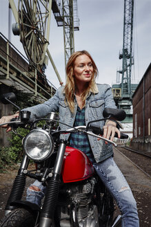 Portrait of smiling young woman on motorcycle - RHF02335