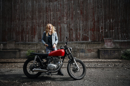 Confident young woman standing next to motorcycle - RHF02338