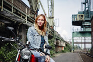 Portrait of confident young woman on motorcycle - RHF02341