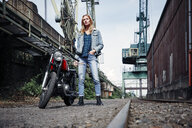 Portrait of confident young woman standing next to motorcycle - RHF02344