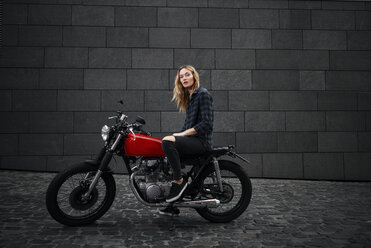 Portrait of confident young woman on motorcycle - RHF02347