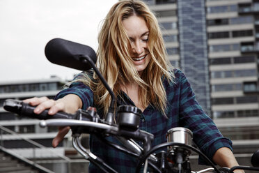 Laughing young woman on motorcycle - RHF02350