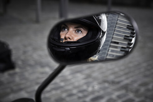 Young woman wearing motorcycle helmet reflected in wing mirror of a motorcycle - RHF02353
