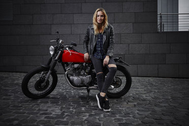 Portrait of confident young woman with motorcycle - RHF02356
