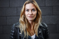 Portrait of confident young woman wearing biker jacket - RHF02359