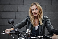 Portrait of confident young woman on motorcycle - RHF02365