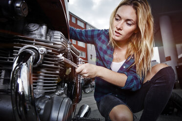 Young woman working on motorcycle - RHF02374
