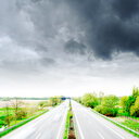 A road passing through greenery under cloudy skies - INGF04280