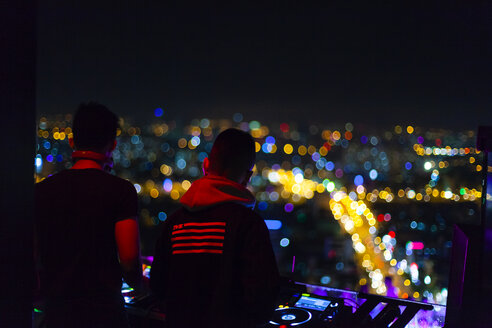 Vietnam, Ho Chi Minh City, Skyline at night, DJ in the foreground - MMA00642