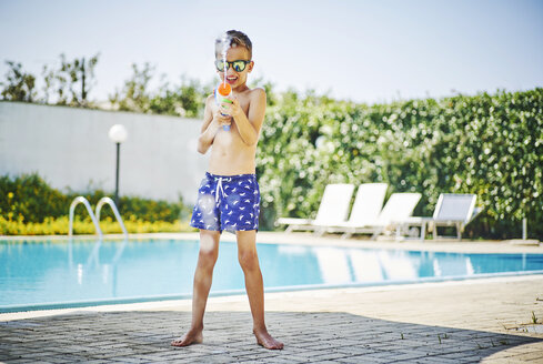 Boy at the poolside with water gun and sunglasses - DIKF00299