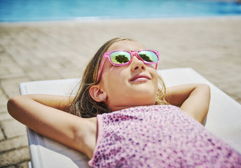 Girl with sunglasses lying at the poolside - DIKF00302