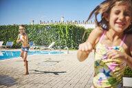 Boy with water gun splashing at girl at the poolside - DIKF00308
