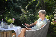 Smiling woman sitting in the garden using digital tablet - BFRF01906