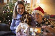 Brother and sister posing for photograph with dog in Christmas gift box - HOXF03955