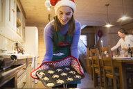 Teenage girl in Christmas Santa hat baking in kitchen - HOXF03958