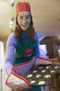 Portrait enthusiastic teenage girl in Christmas apron and paper crown baking muffins - HOXF03961