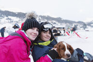 Portrait brother and sister with dog on ski slope - HOXF03964