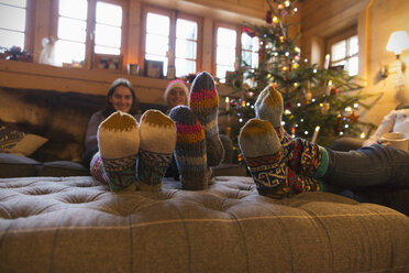 Family with colorful socks relaxing in Christmas living room - HOXF03967