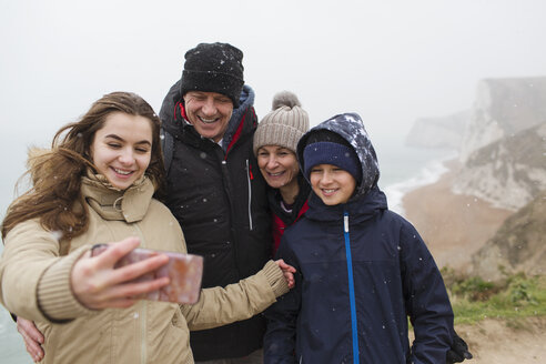 Snow falling over family taking selfie with camera phone - HOXF03982
