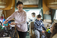Happy family cooking and relaxing in motor home - HOXF03985