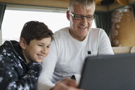 Father and son using digital tablet in motor home - HOXF03991