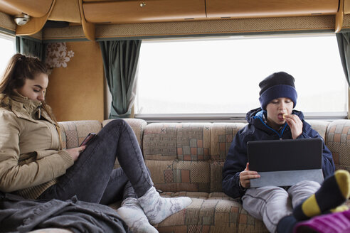 Teenage brother and sister using digital tablet and smart phone in motor home - HOXF03997