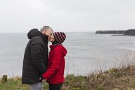 Affectionate couple kissing on cliff overlooking ocean - HOXF04000