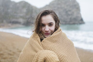 Portrait smiling teenage girl wrapped in blanket on snowy winter beach - HOXF04030