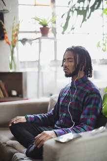 Serene young man meditating with headphones in armchair - HOXF04081