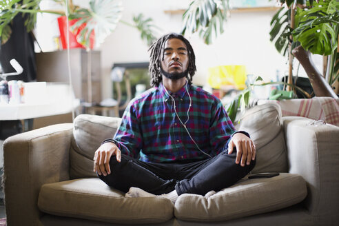 Serene young man meditating with headphones on apartment sofa - HOXF04090