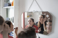 Young women friends getting ready, applying makeup in bathroom mirror - HOXF04093