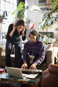 Young man and woman recording music, playing keyboard piano in apartment - HOXF04096