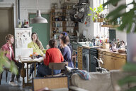 Young college student roommate friends studying at kitchen table in apartment - HOXF04099