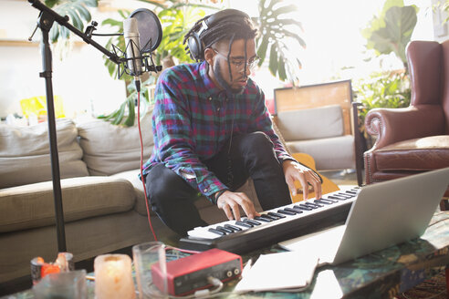 Young man recording music, playing keyboard piano in apartment - HOXF04105