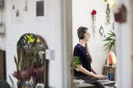 Serene young woman meditating with headphones in apartment - HOXF04108