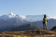 Solo female traveler looking at majestic mountain view, Jaikuni, Indian Himalayan Foothills - HOXF04141