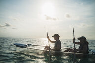 Women in clear bottom canoe on sunny ocean, Maldives, Indian Ocean - HOXF04144
