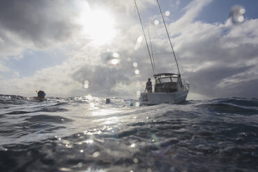 Man snorkeling in sunny ocean near boat, Vava'u, Tonga, Pacific Ocean - HOXF04162