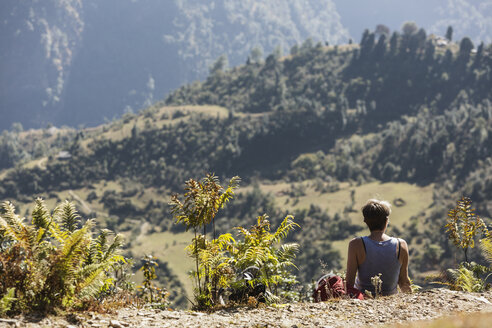 Female hiker resting, enjoying sunny scenic view, Supi Bageshwar, Uttarakhand, Indian Himalayan Foothills - HOXF04171