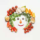 Close-up of salad ingredients forming a face on a white background - INGF05099